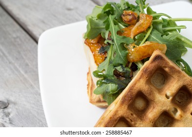Homemade waffle burger on a white ceramic plate against wooden background