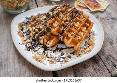 Homemade waffles and granola topped with chocolate sauce in a white plate on the table.