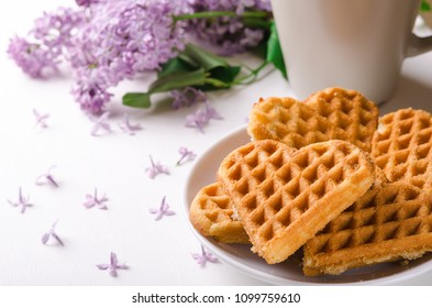 Homemade waffles heart on plate on a white table with flowers. Sweet pastry.