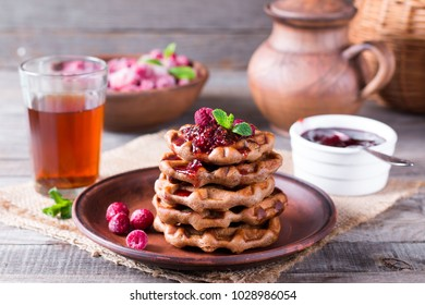 Homemade waffles with jam on an old wooden table. Wafers with a cup of tea