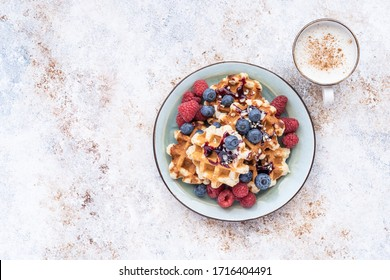 Homemade waffles with raspberries and blueberries on a pink background. Fresh spring flowers. Delicious and healthy Breakfast.