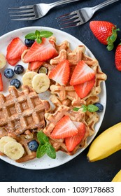 Homemade waffles served with strawberries, blueberries and banana. Top view, closeuo