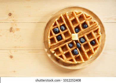 homemade waffles with syrup and  fresh blueberries on wooden table, top view