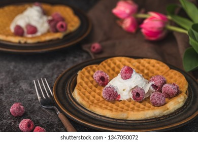 Homemade waffles with whipped cream and organic raspberries. The waffles are on two brown plates on a dark gray background, and there are some red tulips in the background.