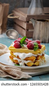 Homemade waffles with whipping cream with raspberries and mint  on plate