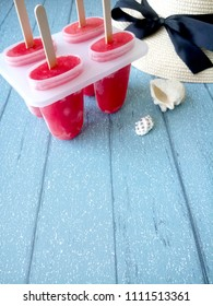 Home-made watermelon popsicles on a blue wooden board.