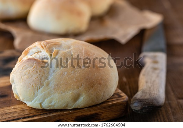 Homemade wheat rolls. Bread knife. Homemade pastries. Cooking and baking together. Bread rolls on the table. Fresh bread.