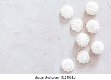 Homemade white meringue on gray concrete background. top view