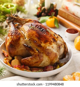 Homemade whole baked Christmas stuffed chicken or turkey served with tangerine for a festive dinner.