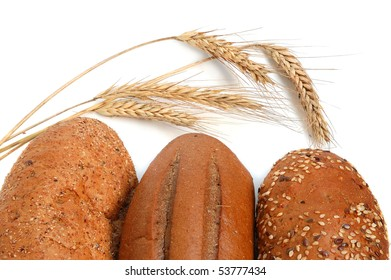 Homemade whole bread and shafts of wheat on a white background