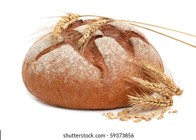 Homemade whole bread and stalks of wheat on a white background