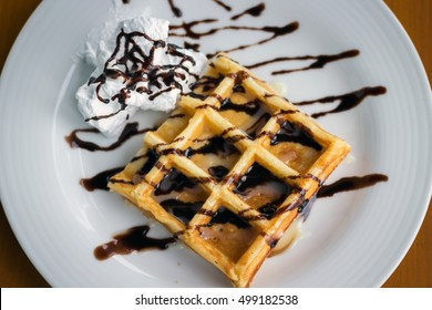 Homemade whole wheat waffle with chocolate sauce and fresh whipping cream; overhead shot