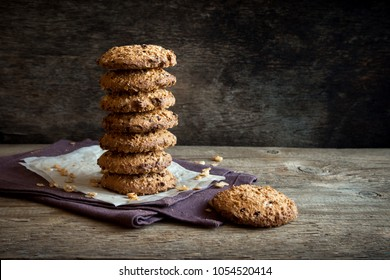 Homemade wholegrain cookies with oatmeal, lin and sesame seeds on dark rustic wooden table, copy space. Healthy vegan wholegrain cookies.