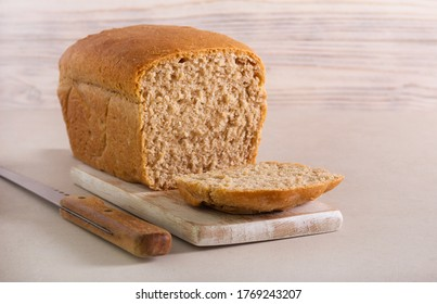 Homemade wholewheat loaf of bread, sliced on board