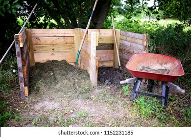 A homemade wooden 2 stage compost bin is constructed in a home garden, with a wheelbarrow and pitchfork sitting close by.