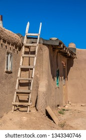 Homemade wooden ladder against side of mud adobe pueblo house where tar paper is being put on roof - with dramatic shadows under intense blue sky