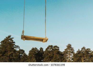 homemade wooden swing against the blue sky and trees,