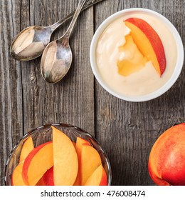 Homemade yogurt with fresh peaches on a wooden background, top view.