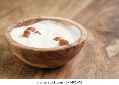 homemade yogurt with hazelnuts in wood bowl on wooden table, shallow focus