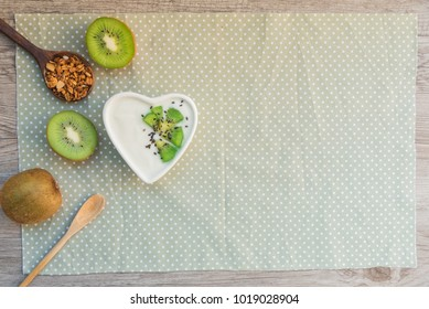 Homemade yogurt kiwi fresh fruits with black sesame and granola in love heart cup on wooden table. Concept about love and relationship. Healthy breakfast, fresh morning with clean diet foods.