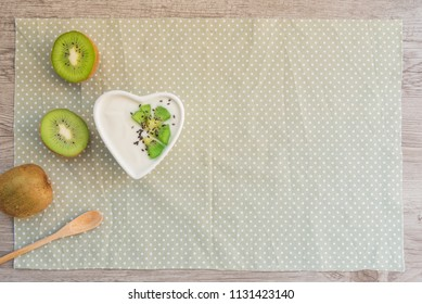 Homemade yogurt with kiwi fresh fruits and black sesame in love heart cup on wooden table. Concept about love and relationship with copy space. Healthy breakfast, fresh morning with clean diet foods.