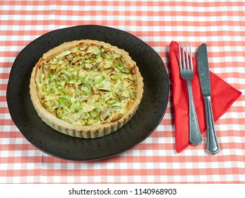 Homemade zucchini, leek and ricotta quiche set on a dark plate, on a red table cloth, with a fork and a knife set on a red napkin