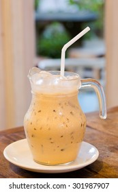 Homemade-style iced coffee latte in glass jar on wooden table