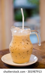 Homemade-style iced coffee latte in glass jar on wooden table, blurry background