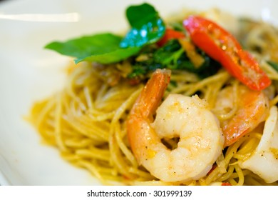 Homemade-Thai-style spicy seafood spaghetti with chili, basil, finger root and kaffir lime leaf (closed-up)