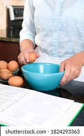 A homemaker cracks an egg into a mixing bowl while following the instructions of a cookbook.