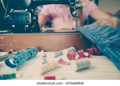 homemaker repairing blue jeans with retro vintage sewing machine at home