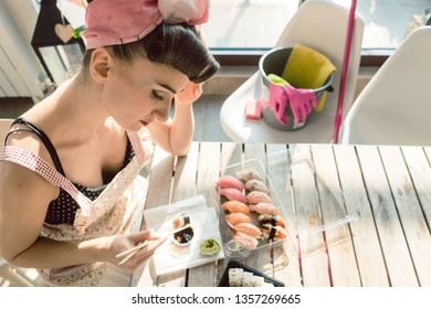 Homemaker woman resting from housework eating some sushi considering her life
