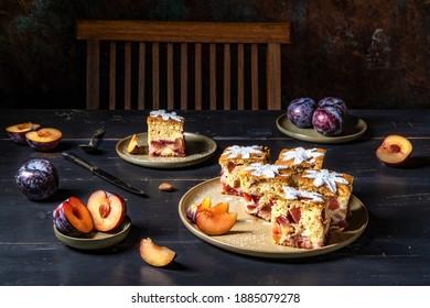Homemamde plum cake servd on plates on a rustic table