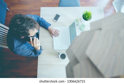 Home-office businessman talking on phone while working,above view