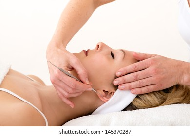 Homeopath using ear acupuncture techniques. Alternative practitioner using ear acupuncture techniques  also called auriculotherapy  on the ear of a beautiful blond woman