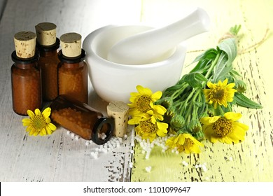 homeopathic arnica pills in brown bottles on wooden background