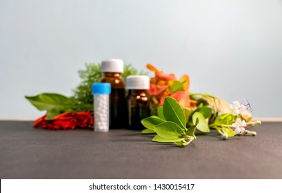 Homeopathic Concept - Blurred image of homeopathic medicine bottles with white,red,orange flowers and green leaves