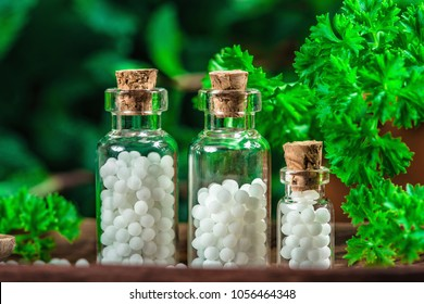 Homeopathic globules in small bottles with fresh leaves in background, homeopathy concept