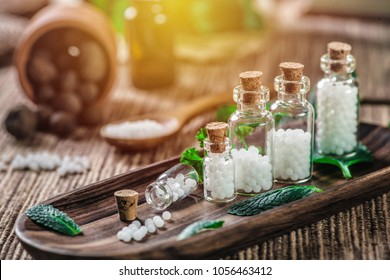 Homeopathic globules in small bottles with mint leaves and wooden spoon in background