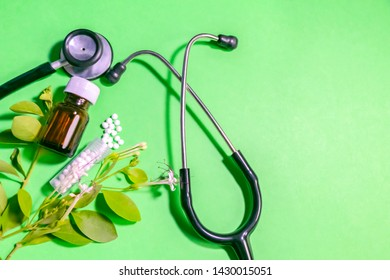 Homeopathic Healing herbs globule pills and a glass bottle on green background with Stethoscope and leaves