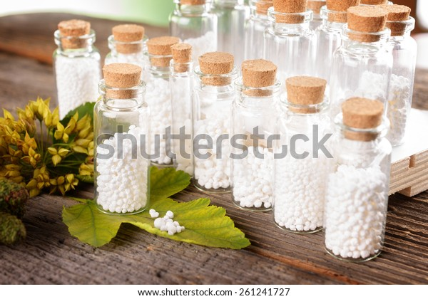 Homeopathic lactose sugar globules in glass bottles with plants