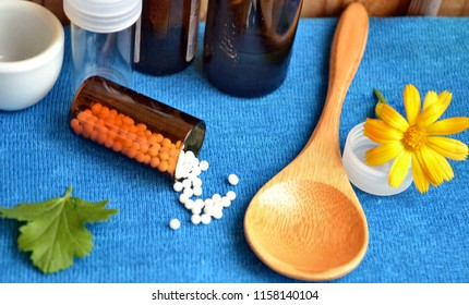 Homeopathic remedies. Alternative medicine. Homeopathic granules. Marigold (Calendula officinalis in Latin) against blue background with wooden spoon, dark and white  glass jars.