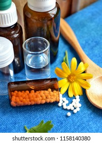 Homeopathic remedies. Alternative medicine. Homeopathic granules. Marigold (Calendula officinalis in Latin) against blue background with wooden spoon, dark and white  glass jars. Vertical view.