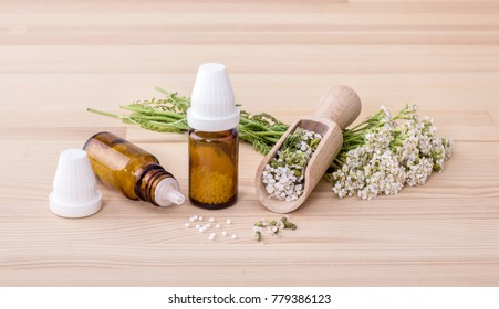 Homeopathic remedy with flowering yarrow and spoon with a wooden background