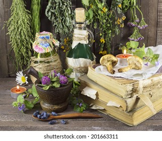 Homeopathic still life with healing herbs, books, glassware and candles