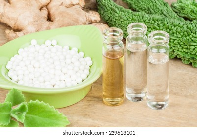 Homeopathy - A homeopathy concept with homeopathic medicine (sugar/lactose pills and liquid homeopathic substances) pictured along with homeopathic vegetables and herbs on a wooden tabletop.