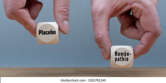 """Homeopathy effect more than the placebo effect? Hand selects cube with the word """"placebo"""" instead of the cube with the German word """"homöopathie"""" (""""homeopathy"""" in English)."""