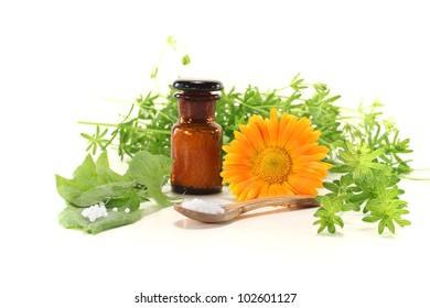 Homeopathy with globules, an apothecary jar, natural herbs and marigolds