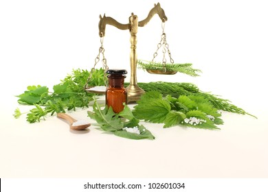 Homeopathy globules, an apothecary jar and scale, and fresh natural herbs