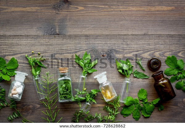 Homeopathy. Leaves of healing herbs, bottles and pills on wooden background top view copyspace